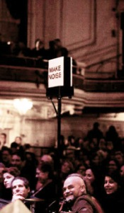The 'Make Noise' applause light in front of the audience at the 2013 taping of Ask Me Another in the Wilbur Theatre, Boston.